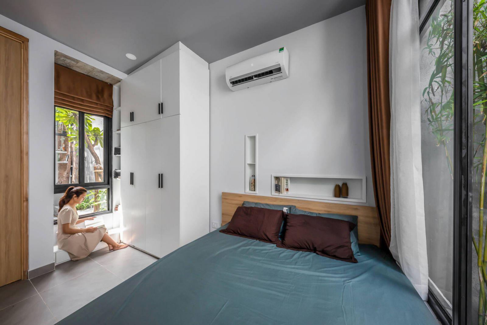 Phòng ngủ đơn giản, gọn gàng với gam màu trắng chủ đạo. Không gian này cũng thoáng đãng nhờ kết nối trực tiếp với 2 khoảng sân vườn ở giữa và sau nhà