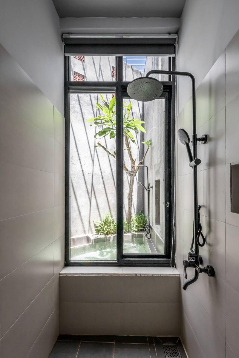 Phòng tắm nhỏ gọn, kết nối trực tiếp với tiểu cảnh hồ nước ở sân vườn phía sau nhà
